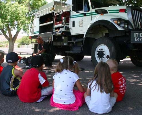 Children listening to speaker in front of truck